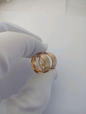 ювелир держит два обручальных кольца