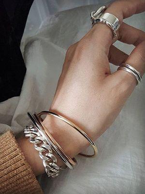серебряные браслеты и кольца на руке