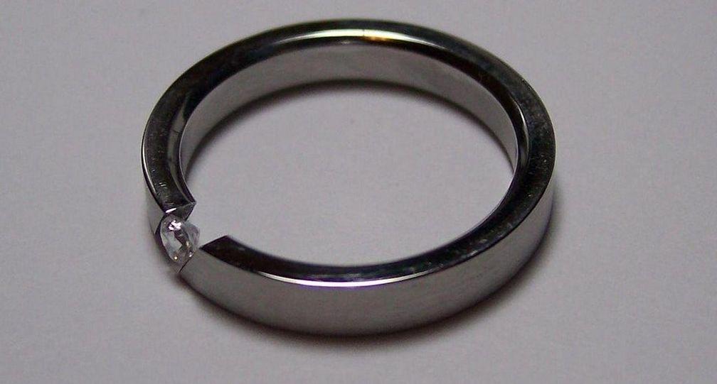 Оправа для обручального кольца из титана с бриллиантом классической огранки в пружинной закрепке