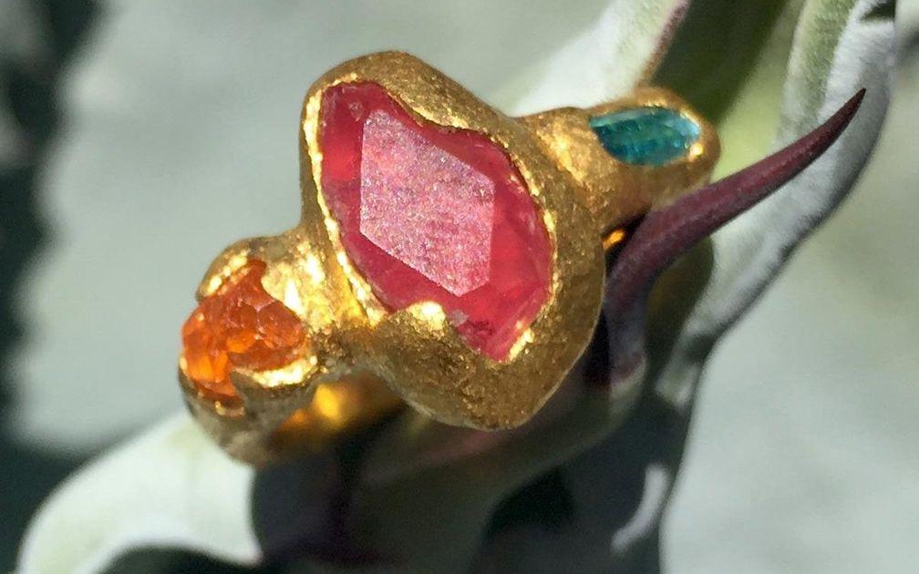 Это уникальное украшение из необработанного камня с пеццоттаитом, спессартитом и турмалином параиба