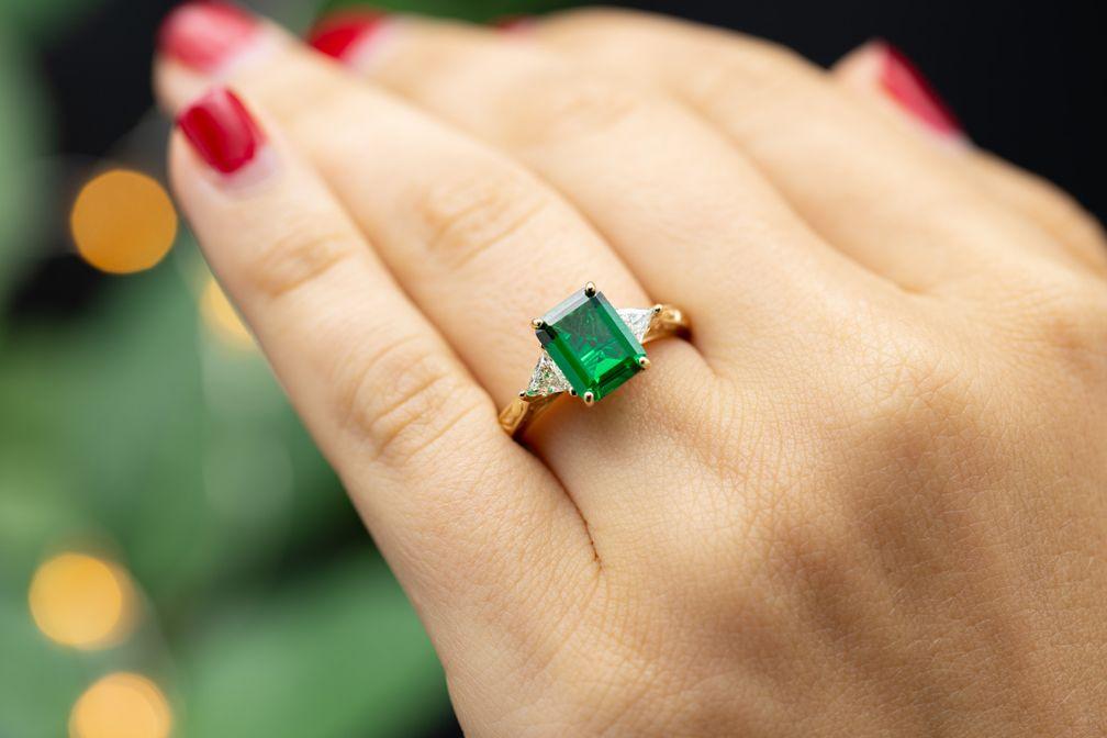 Изумруд с бриллиантами по бокам – классический образ для обручального кольца