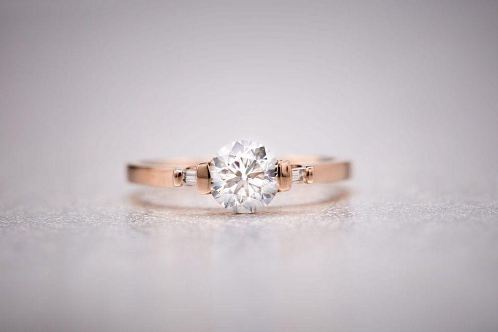Красивый бриллиант круглой огранки в оправе из розового золота с бриллиантами багетной огранки