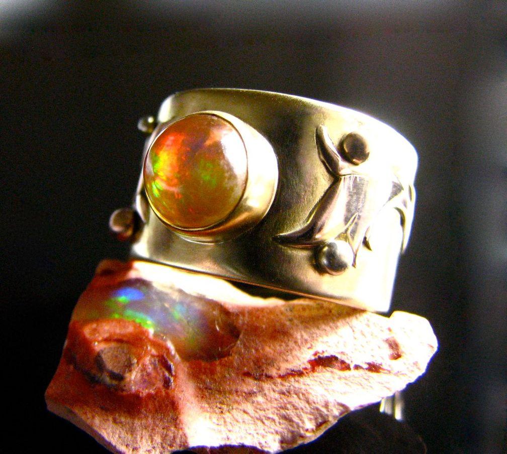 Опаловый кабошон в этом кольце с игрой цвета на желто-оранжевом корпусе обязательно вызовет комплименты