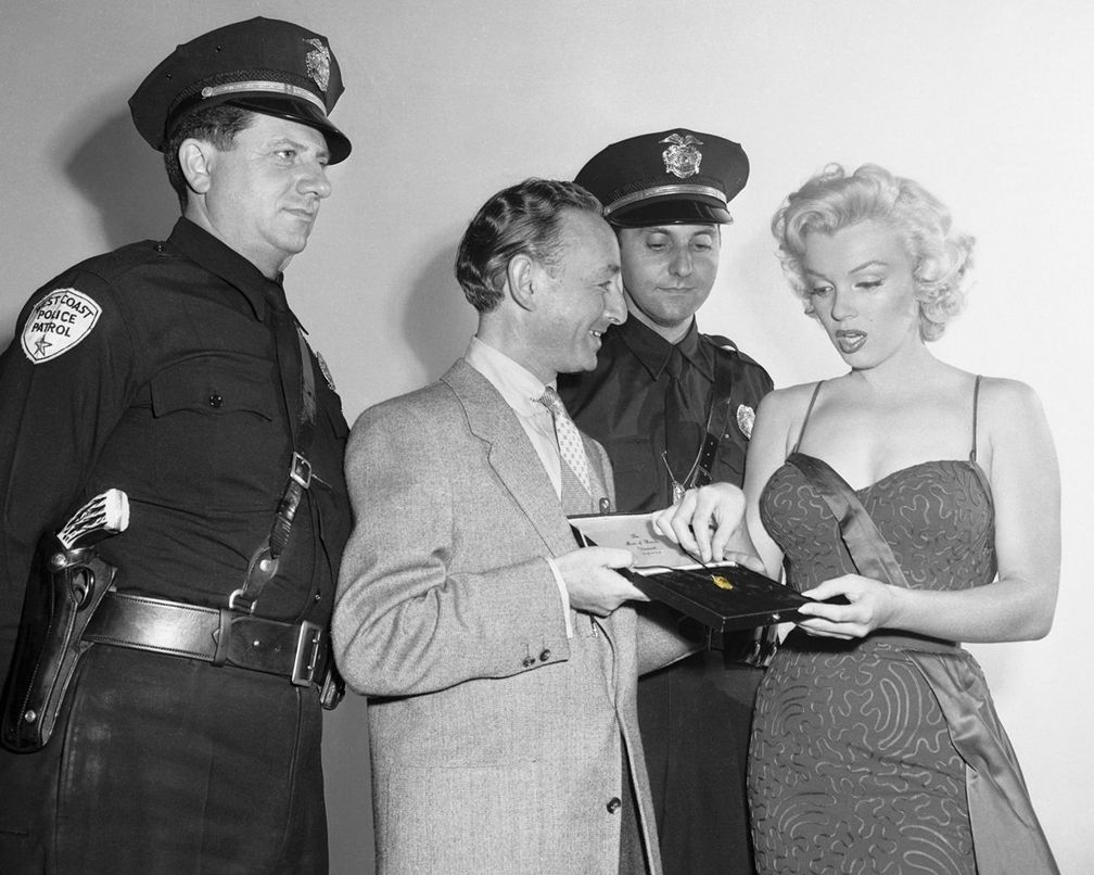 Представляя Ювелирную академию, Мэнни Липпетт из Санта-Моники показывает Мэрилин Монро знаменитый бриллиант «Луна Бароды»